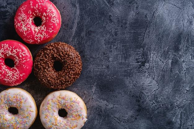 Ciambelle al cioccolato, rosa e vaniglia con granelli, dolce cibo da dessert glassato su cemento scuro testurizzato, copia vista dall'alto