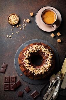 Ciambella al cioccolato e zucca con glassa al cioccolato e noci su fondo di cemento scuro.