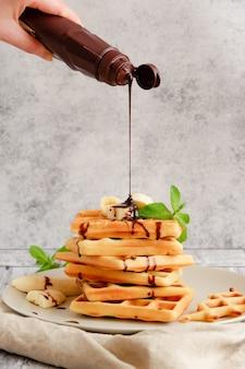 Salsa di cioccolato che viene versata a mano su cialde belghe con banana