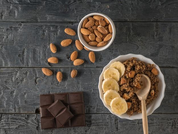 Cioccolato, mandorle sparse e porridge di quinoa su un tavolo di legno. dieta sana. disposizione piatta.