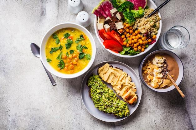 Ciotola di frullato al cioccolato, ciotola di buddha con tofu, ceci e quinoa, zuppa di lenticchie e toast