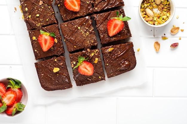 Quadratini di cioccolato con pistacchi e fragole su carta bianca