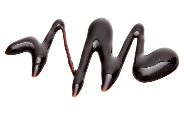 Goccia di sciroppo di cioccolato isolata su sfondo bianco