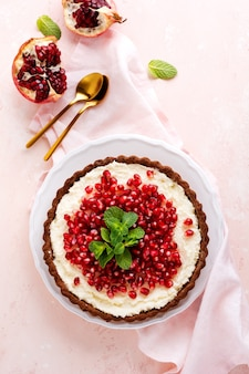 Crostata al cioccolato con crema di cocco e melograno e menta su uno sfondo rosa da tavola. dolce fatto in casa. vista dall'alto
