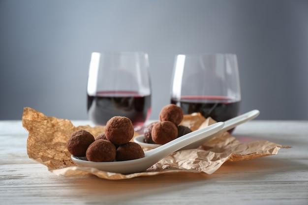 Tartufi di cioccolato e bicchieri con vino rosso sul tavolo