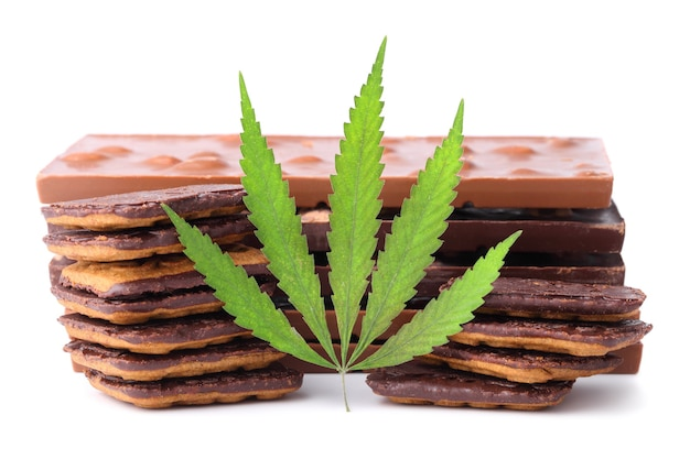 Cioccolato con estratto di marijuana, biscotti al cioccolato con contenuto di cbd. barrette di cioccolato con noci e contenuto di cannabis cbd, foglia di canapa verde.