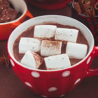 Cioccolato con marshmallow in tazza rossa a pois