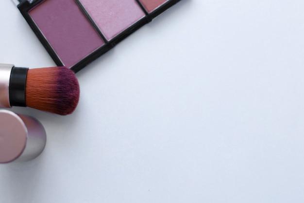 Un bronzer color cioccolato e un illuminante e un pennello per applicare il blush su uno sfondo bianco con...