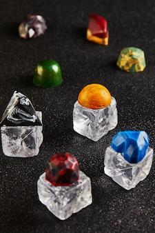 Cioccolatini sotto forma di pietre preziose su cubetti di ghiaccio.