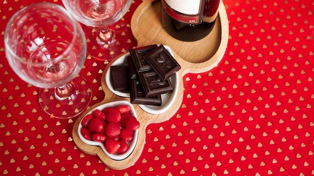 Cioccolatini e dolci su piatti a forma di cuore. impostazione della tavola festiva per la data degli innamorati. sfondo rosso