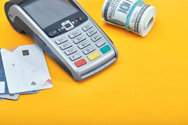 Scelta tra banconote da cento dollari e carte di credito su sfondo giallo.
