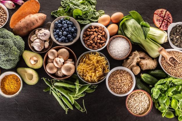 Scelta di cibi freschi e alimentazione sana: verdura, frutta, legumi e cereali su un tavolo di cemento - vista dall'alto.