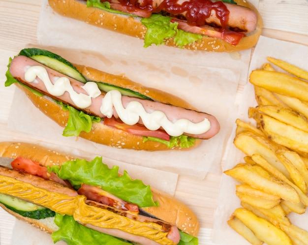 Scelta di tre diversi hot dog con guarnizioni assortite di insalata fresca condite con senape, maionese o senape viste dall'alto con patatine