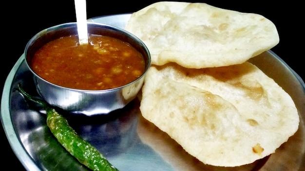 Chole bhature: piatto indiano speziato al curry di ceci noto anche come chole o chana masala è una ricetta tradizionale del piatto principale dell'india settentrionale e solitamente servita con puri fritti / bhature