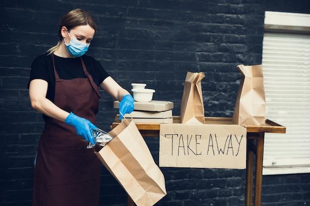 Scegli la salute. donna che prepara bevande e pasti, indossa una maschera protettiva, guanti. servizio di consegna senza contatto durante la pandemia di coronavirus in quarantena. porta via il concetto. tazze riciclabili, confezioni.