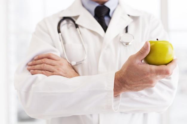 Scegli uno stile di vita sano! immagine ritagliata del dottore in uniforme bianca che tiene una mela