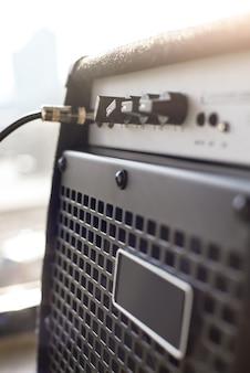 La scelta dell'amplificatore per chitarra. vista ravvicinata verticale dell'amplificatore per chitarra con cavo audio jack. strumenti musicali. attrezzature musicali