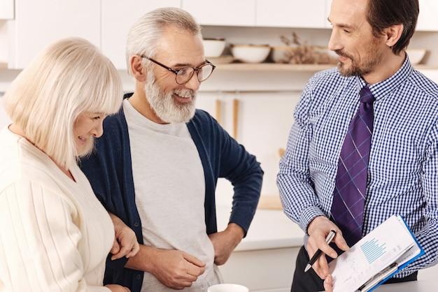 Scelta delle varianti di investimento. agente immobiliare positivo qualificato e ottimista che parla con una coppia di clienti anziani mentre presenta il contratto per l'investimento in un appartamento ed esprime gioia