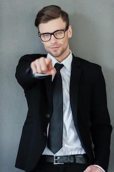 Scegliendo te. fiducioso giovane uomo d'affari che punta alla telecamera