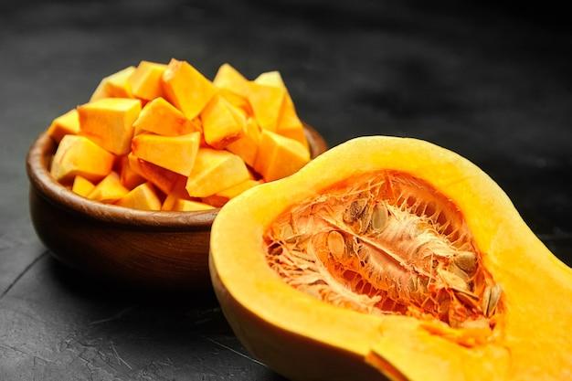 Zucca di butternut tritata, metà della zucca, pezzi della verdura fresca nella ciotola di legno sulla tavola di pietra nera, fuoco selettivo. ingrediente alimentare