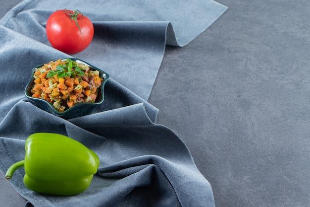 Carote e fagioli tritati in una ciotola accanto a pepe e pomodori su un asciugamano, sullo sfondo di marmo.