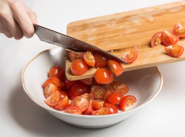 I pomodorini tagliati vengono trasferiti in un'insalatiera.