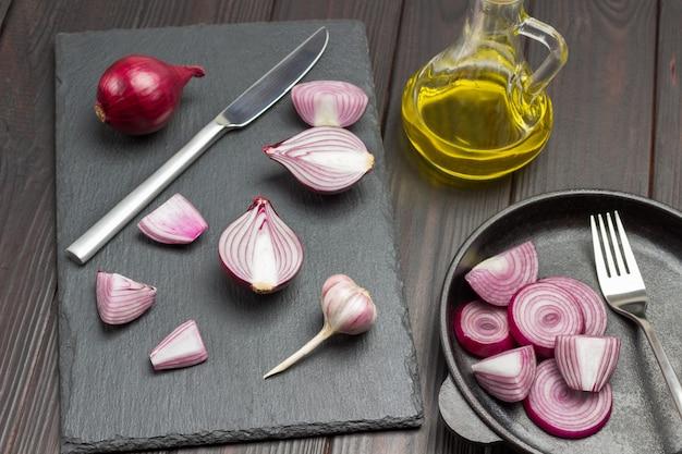 Cipolla tritata, coltello e una cipolla intera sul tagliere. cipolle tritate e forchetta in padella. bottiglia di olio. fondo in legno scuro. vista dall'alto