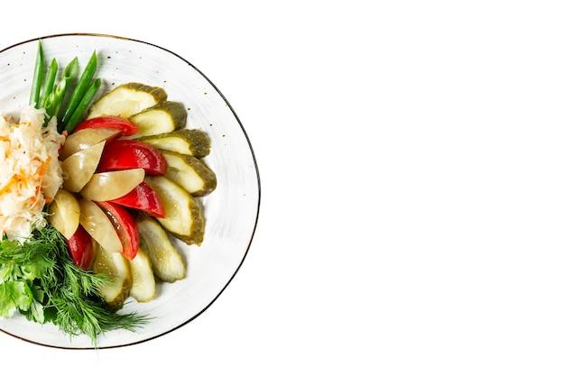 Sottaceti tritati su un piatto. cavolo fermentato, pomodori, cetrioli e peperoni con un mazzetto di verdure. isolato su sfondo bianco. spazio per il testo.
