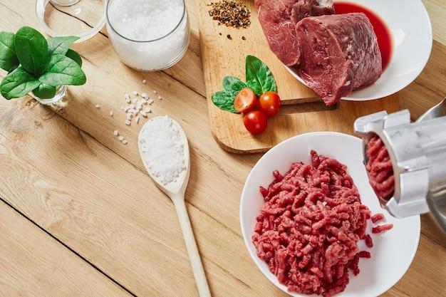 Carne cruda tritata e carne macinata. il processo di preparazione della carne forzata da un tritacarne. vista dall'alto.