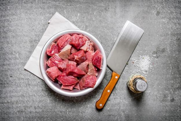 Carne cruda tritata con un coltello da macellaio e sale sul tavolo di pietra
