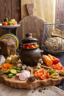 Verdure tritate per zuppa e una pentola di ceramica