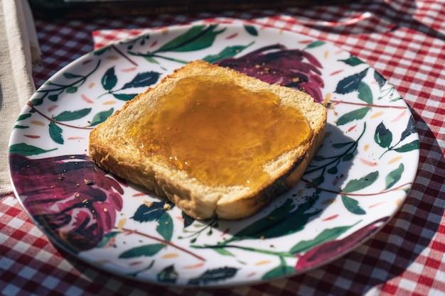 Vista tritata di un piatto con un toast spalmato con marmellata di pesche.