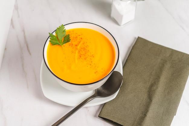 Vista tritata di una ciotola bianca con crema di zucca e zuppa di carote con un tovagliolo verde