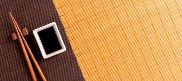 Bacchette e ciotola con salsa di soia su due blak stuoia di bambù e giallo vista dall'alto con lo spazio della copia.