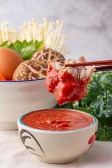 Le bacchette hanno raccolto il maiale immerso in una ciotola di salsa sukiyaki, molte verdure nella ciotola bianca includono carote, mais, funghi shiitake, aghi dorati, sedano e uova di gallina.