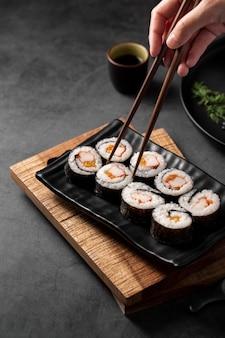 Bacchette raccogliendo involtini di sushi maki