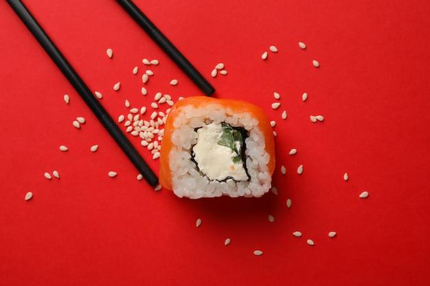 Bacchette e rotolo di sushi su superficie rossa
