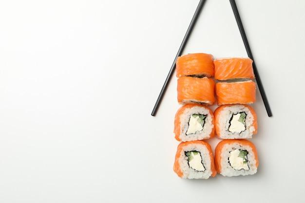 Bacchette e rotoli di sushi su superficie bianca
