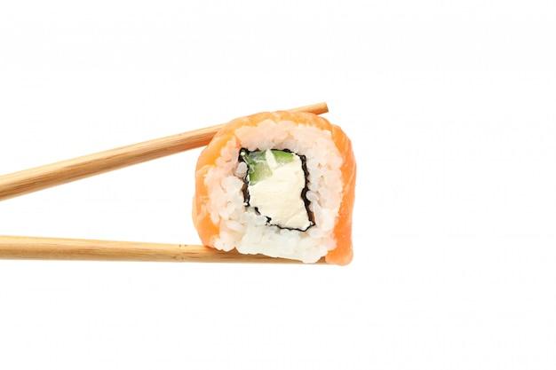 Bastoncini con il rotolo di sushi isolato su superficie bianca