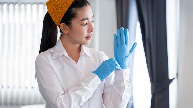 Concetto di routine una casa della moglie in abiti modesti che indossa guanti di lattice per proteggersi dal germe prima di pulire le stanze dell'ufficio.