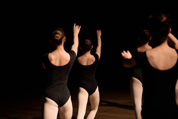 Una coreografia di un gruppo di graziose e graziose ballerine che si esercitano sul palco di una scuola di danza classica.