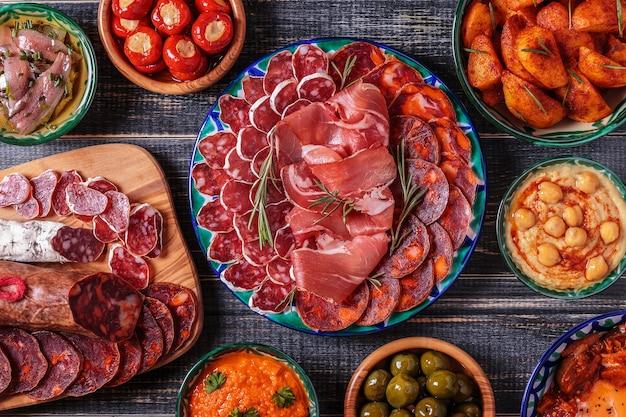 Chorizo, salame, ciotole con olive, peperoni, acciughe, patate piccanti, purè di ceci su un tavolo di legno.