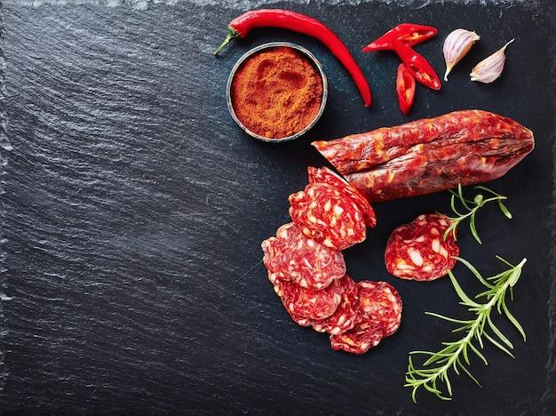 Salsiccia chorizo tagliata a fette su una lastra di ardesia nera con paprika affumicata, peperoncino affettato e rosmarino fresco, vista da sopra, close-up, flatlay, spazio di copia
