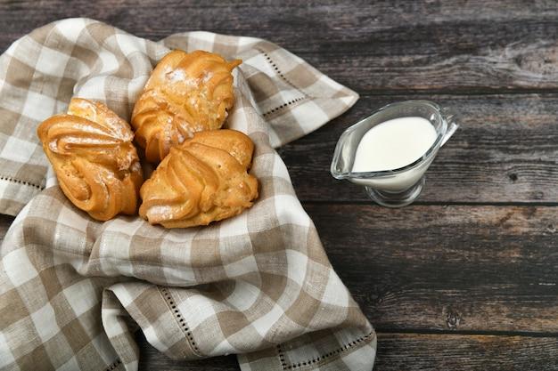 Torta di choux con latte su un legno scuro. in un cestino su un asciugamano a scacchi. . chic con ricotta. la piccola crema pasticcera agglutina in ciotola di vimini su di legno