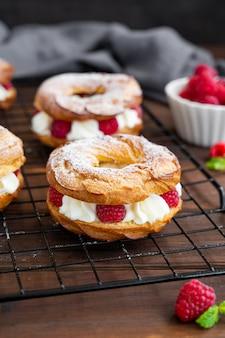 Bignè anelli di bignè con crema di formaggio cremoso o ricotta e lamponi freschi