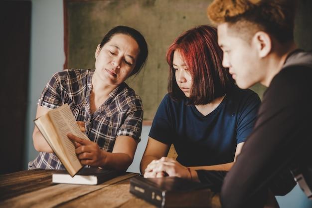 Chris mamma e figlia con figlio studiano e leggono. il concetto di cristianesimo.