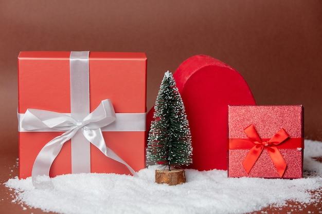 Albero di natale su una neve con scatole regalo