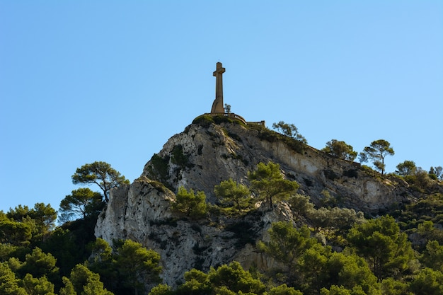 Croce cristiana sulla cima rocciosa di una montagna piena di pini