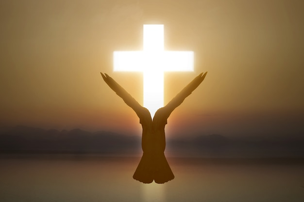 Christian cross e silhouette di piccione con uno sfondo di cielo di alba Foto Premium
