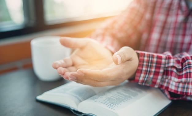 Mano cristiana durante la preghiera e l'adorazione per la religione cristiana con sfocato dello sfondo del suo corpo, uomo casuale che prega con le mani insieme su una bibbia chiusa. sfondo cristiano. la libertà.